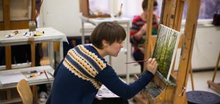 Nainen maalaa keskittyneenä taulua