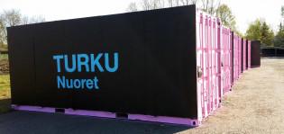 Päällystetyt kontit nurmella, kontissa logo Turku Nuoret