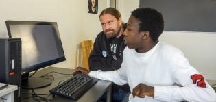 Mies opastaa nuorta tietokoneella.